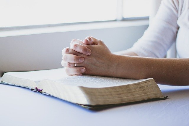 Woman with hands together prayer with bible